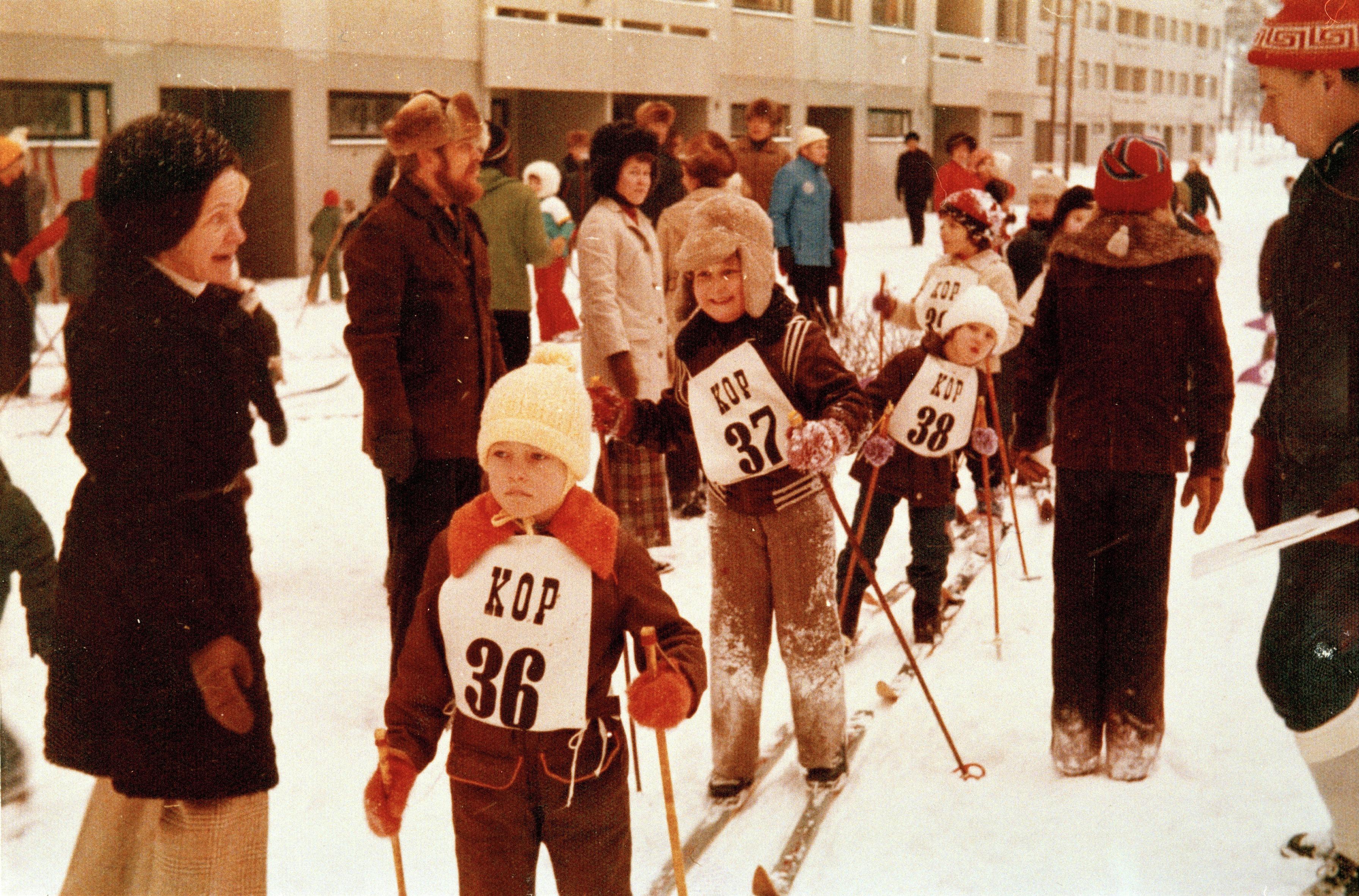 Lapsia lähtövalmiina hiihtokilpailuun kerrostalon pihalla Kontulassa, ympärillä vanhempia. Helsingin kaupunmuseo.